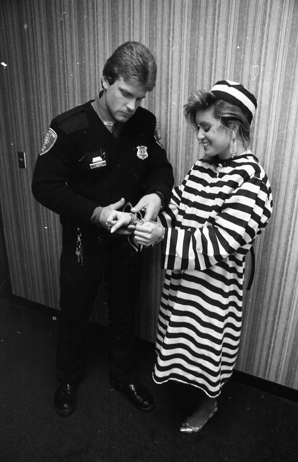 "RJ file photo - ""Jail and Bail"" Chairman Julie Blichfeldt is put in handcuffs by Wallingford Police officer Ted Weimer. The fundraiser for the American Cancer Society is being held at the Britannia Spoon Co., Feb. 1989."