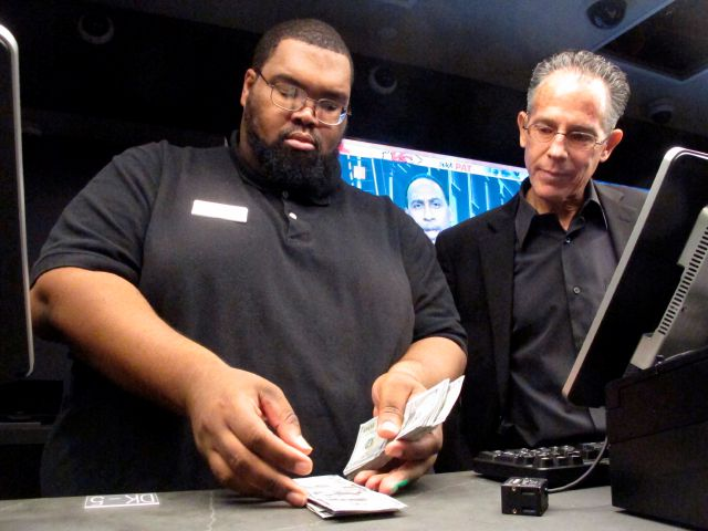 Lance Weekes, a clerk at the DraftKings sports book at Resorts Casino in Atlantic City N.J. counts money on the first day the facility began taking sports bets on Nov. 20, 2018. Numerous U.S. states are considering joining the seven that currently offer legal sports betting. (AP Photo/Wayne Parry)