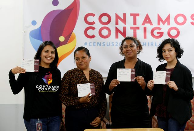 In this Friday, April 26, 2019, photo, Esperanza Guevara, left, census campaign manager for the Coalition for Humane Immigrant Rights, poses with volunteers Angeles Rosales, second from left, Janet Mendez and Los Angeles organizer Diana Escamilla, right, at their office in Los Angeles, as they each hold census campaign cards. States are spending millions of dollars on outreach and promotion, connecting with nonprofits and working with cities in an effort to ensure that as many of their residents as possible are counted in the upcoming census. The likelihood that Hispanics and other immigrants could be scared off by a citizenship question has some states redoubling those efforts. (AP Photo/Damian Dovarganes)