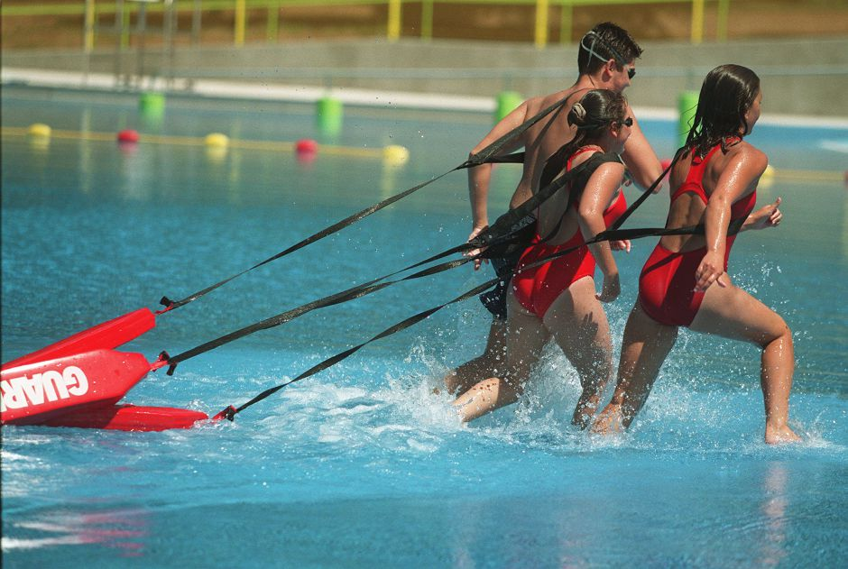 Lifeguards Erik Brandl, left, Camila Gabriel, center, and Sarah Hvizd, right, run out of the pool towing their rescue tubes at the Community Pool in Wallingford. The lifeguards practiced some lifesaving drills Tuesday afternoon July 20, 1999. The pool is not yet open.
