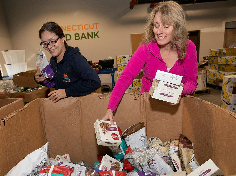 Deborah Cruz, of Windsor, left, and Terry Lee, of Wallingford, pull food items from a donation box while volunteering at the Connecticut Food Bank.