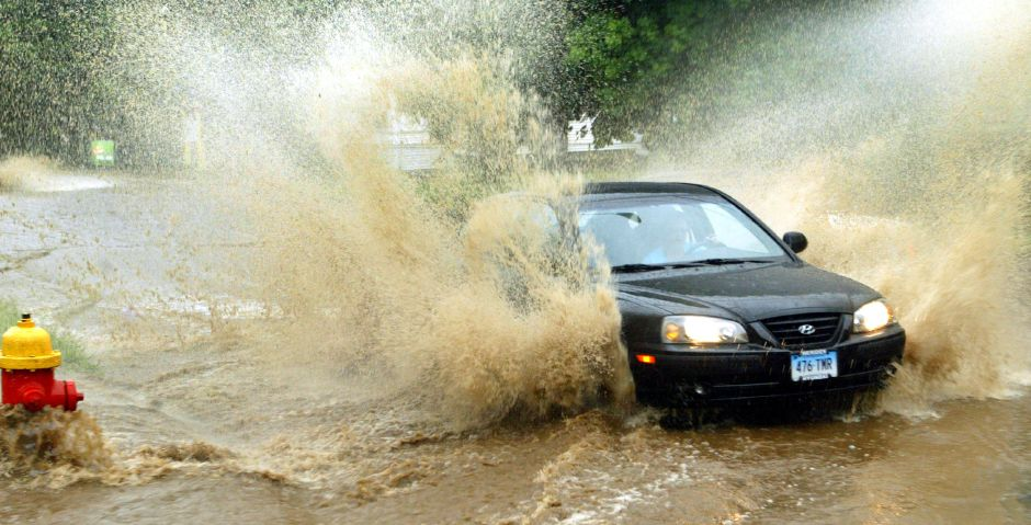 A motorist takes on flooding at the intersection of Johnson and Allen Avenue
