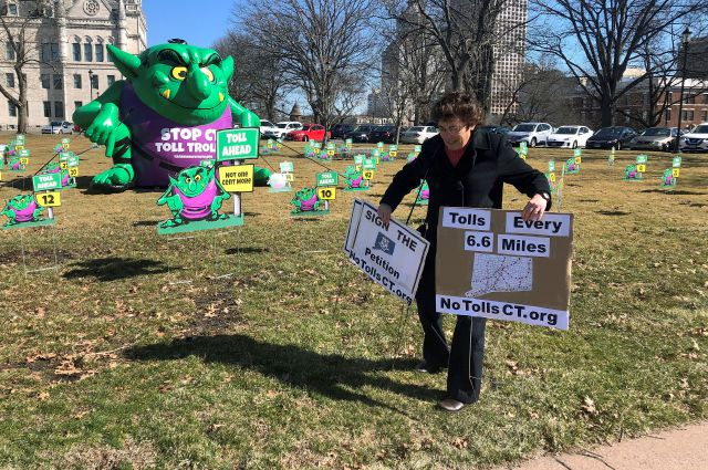 "Joanne Baker of Woodstock carries two signs showing her opposition to proposed tolls on Connecticut highways, Tuesday, March 19, 2019, outside the Connecticut State Capitol in Hartford, Conn. The conservative Yankee Institute for Public Policy erected a large ""Toll Troll"" on the front lawn of the Capitol ahead of a planned committee vote on tolls. (AP Photo/Susan Haigh)"