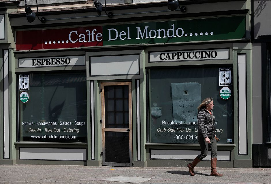 A woman walks by Caffe Del Mondo at 51 N. Main St. in Southington on Thursday. The business has been closed since the beginning of the year. Photos by Dave Zajac, Record-Journal