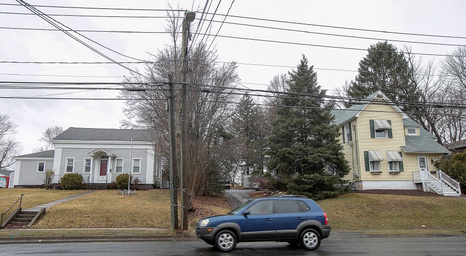 A motorist travels past 19th century homes at 60 Broad St., left, and 66 Broad St., right, in Meriden on Friday.  A Harwinton developer won Planning Commission approval last week to build a retail building at 60 and 66 Broad St.