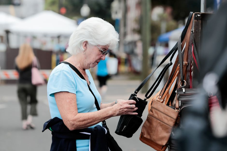 Eileen Johnson of Northford looks at a leather purse Sunday during the Arts and Crafts show at the Apple Harvest Festival in Southington October 7, 2018 | Justin Weekes / Special to the Record-Journal