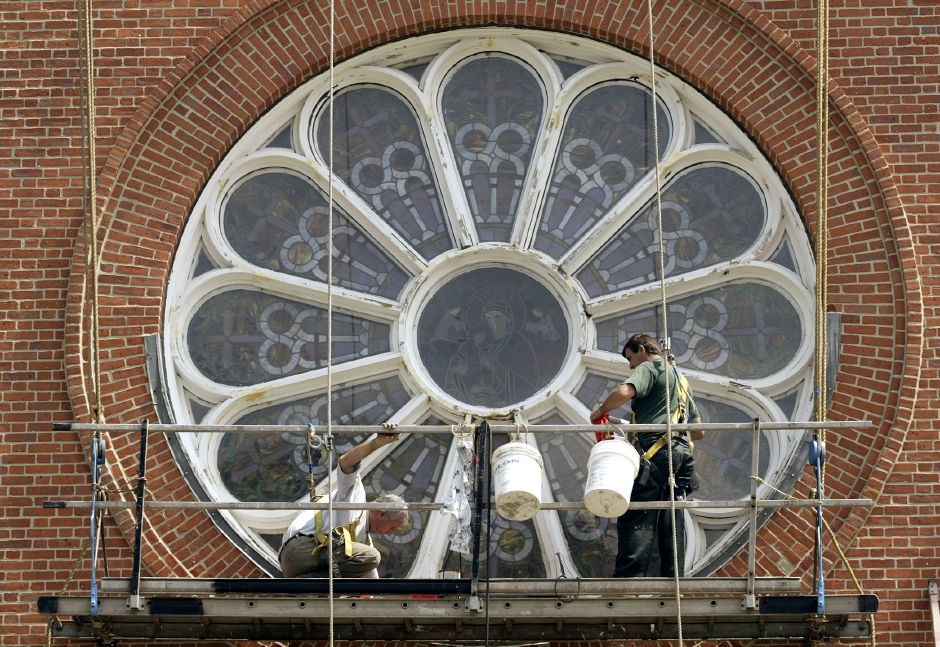 New England Masonry Company of Naugatuck workers Mehmet Gashi (cq) and Hisni Dobruna (cq) rest on a scaffolding as they do chalk repairs to a large oval stained glass window at St. Stanislaus Church on Olive street in Meriden on Thursday afternoon.