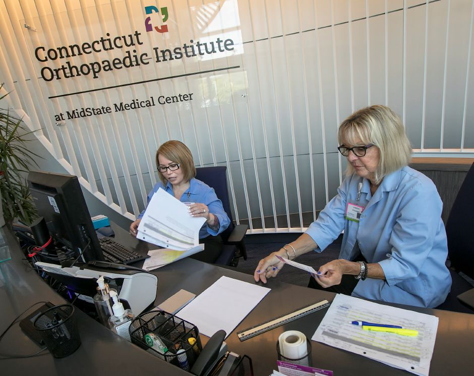 Marisol Carrero, financial counselor, left, and Cheryl Solecki, volunteer, work at the front desk of the Connecticut Orthopaedic Institute at MidState Medical Center in Meriden, Tuesday, May 15, 2018. Dave Zajac, Record-Journal