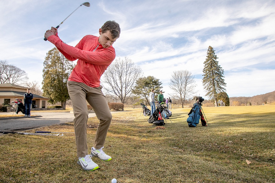 Meriden residents Benjamin Pierce, 17, above, and Joshua Farnsworth, 16, below, take shots at the  practice green at Hunter Golf Club in Meriden on Monday. The course opens Wednesday.                                                                Photos by Dave Zajac, Record-Journal