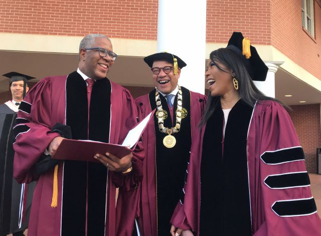 Robert F. Smith, left, laughs with David Thomas, center, and actress Angela Bassett at Morehouse College on Sunday, May 19, 2019, in Atlanta. Smith, a billionaire technology investor and philanthropist, said he will provide grants to wipe out the student debt of the entire graduating class at Morehouse College - an estimated 40 million. Smith, this year