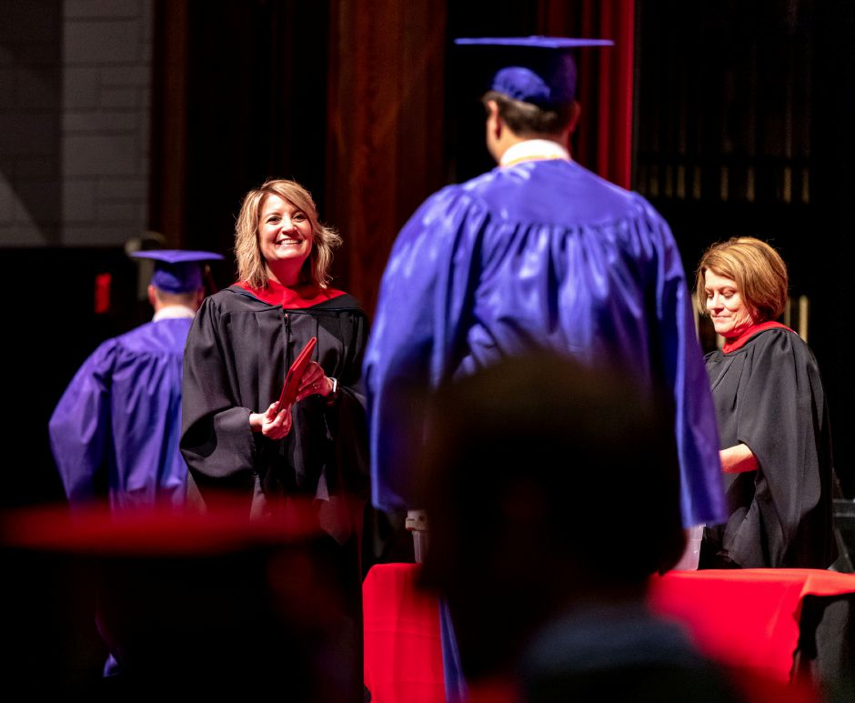 Berlin High School Principal Eileen Eustis prepares to hand a student his diploma during the 2019 cermony, held at Central Connecticut State University on June 16, 2019. | Devin Leith-Yessian/Record-Journal