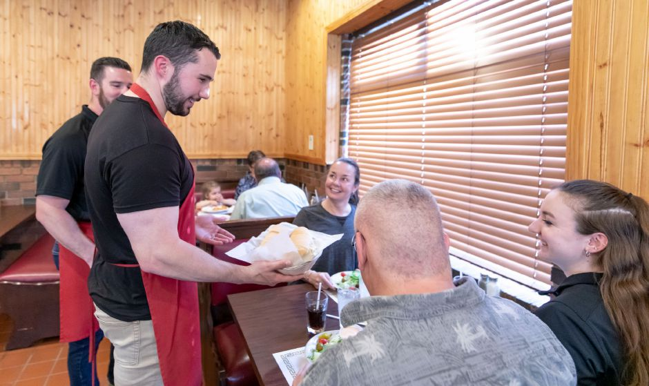 Berlin police Officer Brett Kelly serves customers at Central Pizza during the department