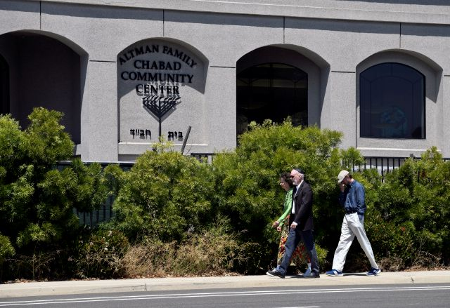 "FILE - In this April 27, 2019 file photo, synagogue members walk outside of the Chabad of Poway Synagogue in Poway, Calif. The gunman who attacked the synagogue last week fired his semi-automatic rifle at Passover worshippers after walking through the front entrance that synagogue leaders identified last year as needing improved security. The synagogue applied for a federal grant to better protect that area. The money, 150,000, was approved in September but only arrived in late March. ""Obviously we did not have a chance to start using the funds yet,"" Rabbi Scimcha Backman told The Associated Press. (AP Photo/Denis Poroy)"