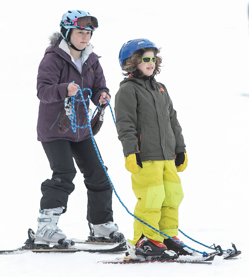 Quinnipiac University student Emma Poulshock assists Jasper Costello, 8, of Branford, during Skiers Unlimited at Mount Southington. Dave Zajac, Record-Journal