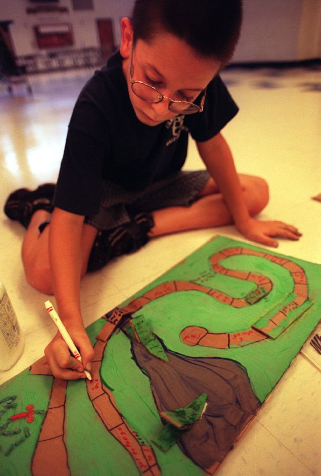 Peter Soul, age 9, paints the game he has been making in French class at the Wallingford Language Arts summer program held at Moran Middle School July 28, 1999.