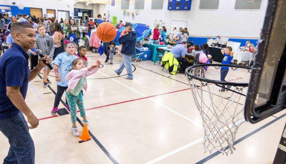 Madison Moneymaker, 6, of Southington, launches a basketball at the Plainville Family Fest on Saturday, May 20, 2018. The event featured facepainting, a large set of model trains and dozens of vendors and organizations with tables throughout the halls of Linden Street School. | Devin Leith-Yessian/Plainville Citizen