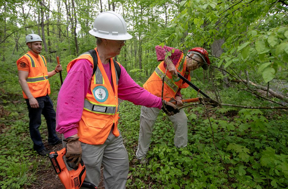 Dianne Saunders, Conservation Commission member, center, assists fellow member Dianne Lendler who clips a branch overhanging a trail in the Tyler Mill Preserve in Wallingford, Fri., May 17, 2019. Visitors will see dramatic differences next week to the landscape of Tyler Mill Preserve, which is slated to reopen after being closed for a year. Dave Zajac, Record-Journal