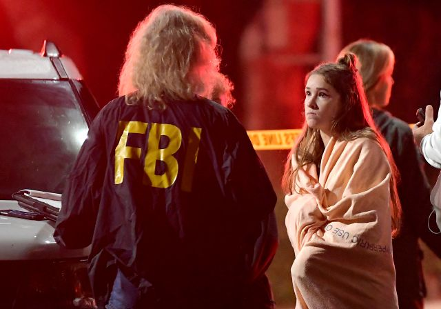 "An FBI agent talks to a potential witness as they stand near the scene Thursday, Nov. 8, 2018, in Thousand Oaks, Calif. where a gunman opened fire Wednesday inside a country dance bar crowded with hundreds of people on ""college night,"" wounding 11 people including a deputy who rushed to the scene. Ventura County sheriff"