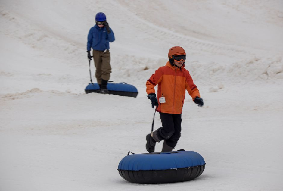 Garetson Curtis, 12, of New Haven runs towards the conveyor belt after going down the tubing slopes with his friend David Carroll, 12, of Branford.