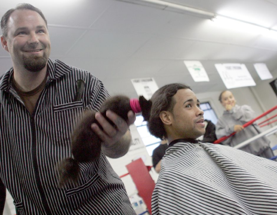 FILE PHOTO — Glenn Agnew, Barber/Owner of Village Barber Shop, tosses a long section of hair of Meriden resident Jose Lara 21, right, to his mother at Beat the Street Community Center. Lara said he hadn