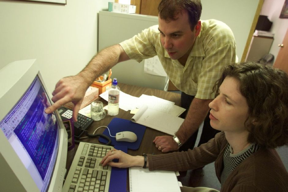 RJ file photo - Seth Brewer of Glastonbury, left, tries to figure out a few bad lines of code with programmer Noga Manela, of New Haven at the Innovative internet marketing in Wallingford, May 1999.
