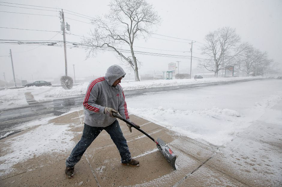 Josue Feliciano, working for Waterbury based Independent Crushing, clears the sidewalk in front of the Silver Commons on South Broad Street in Meriden, Tuesday, March 13, 2018. Dave Zajac, Record-Journal