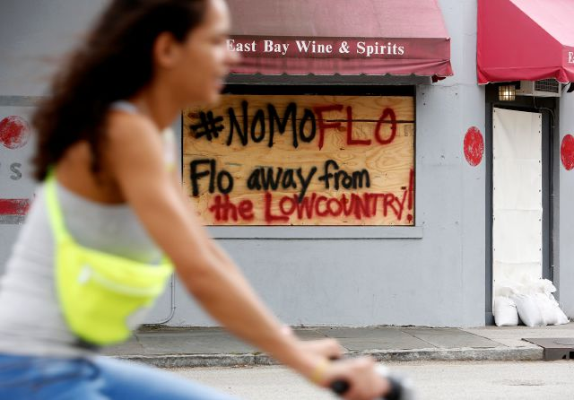 A bike rider makes her way down East Bay St. past a sign asking for Hurricane Florence to spare the Lowcountry in Charleston, S.C., as Hurricane Florence spins out in the Atlantic ocean Thursday, Sept. 13, 2018. (AP Photo/Mic Smith)