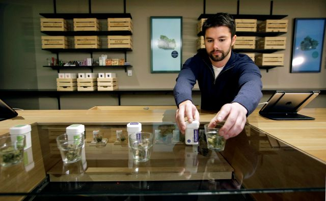 Sam Barber, president and CEO of the Cultivate dispensary, arranges smokable strains of cannabis before opening on the first day of legal recreational marijuana sales, Tuesday, Nov. 20, 2018, in Leicester, Mass. Cultivate is one of the first two shops permitted to sell recreational marijuana in the eastern United States, more than two years after Massachusetts voters approved it in 2016. (AP Photo/Steven Senne)