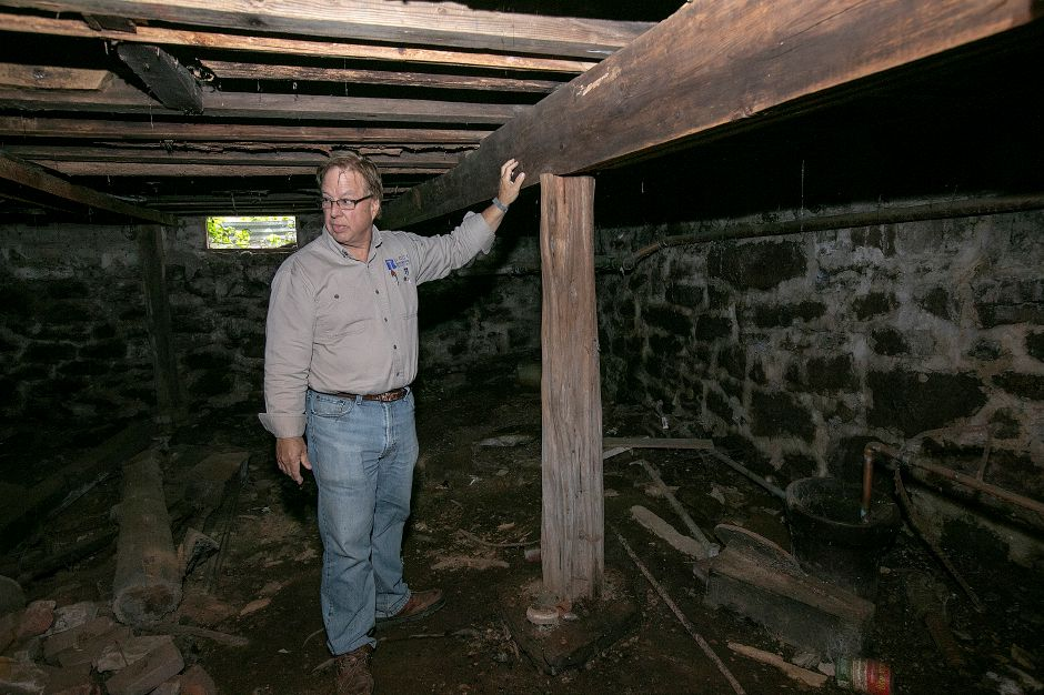 Local developer John Ricci talks about cedar tree supports in the basement of the Nathaniel Ives house at 257 Fenn Rd. in Cheshire, Monday, Oct. 8, 2018. Ricci is owner of the house built around 1749 and is considering how to develop the 50-acre property. Dave Zajac, Record-Journal