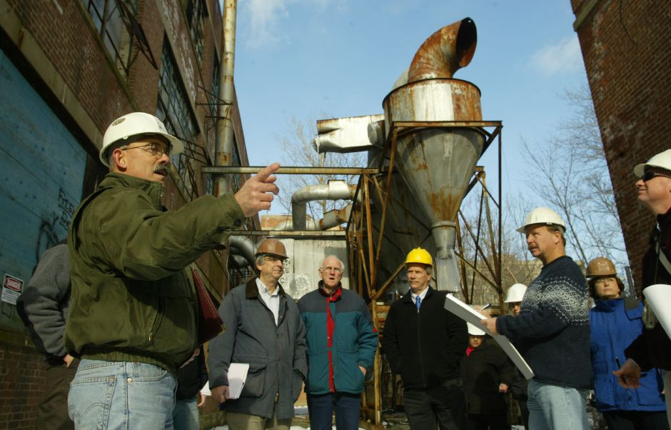 Joseph Santovasi of Advanced Environmental Interface, Inc., left, talks to a group of local and state officials touring the defunct Factory H off Cherry Street in Meriden January 10, 2006. Santovasi is project manager on the site. (dave zajac photo)