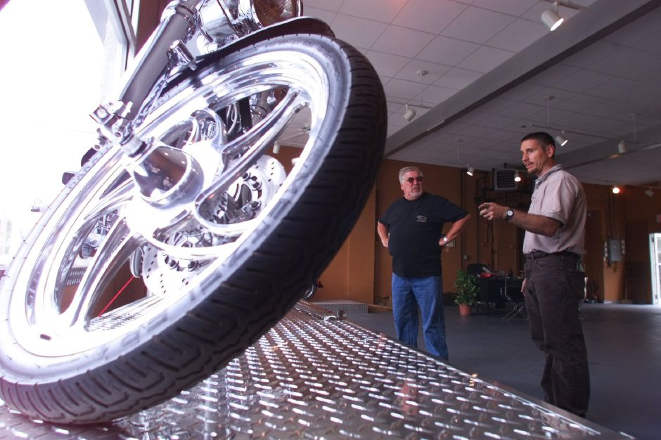 Anthony Milici, right, owner of the Mad Dog Motorcycle dealership in Wallingford talks to Bob Pitts, of Lake Placid, NY, about the bike in the foreground, a Pure Steel motorcycle, July 27, 1999 Bob was looking for a bike and the Pure Steel bikes are quite the thing. This one is around $40,000 but Anthony says it