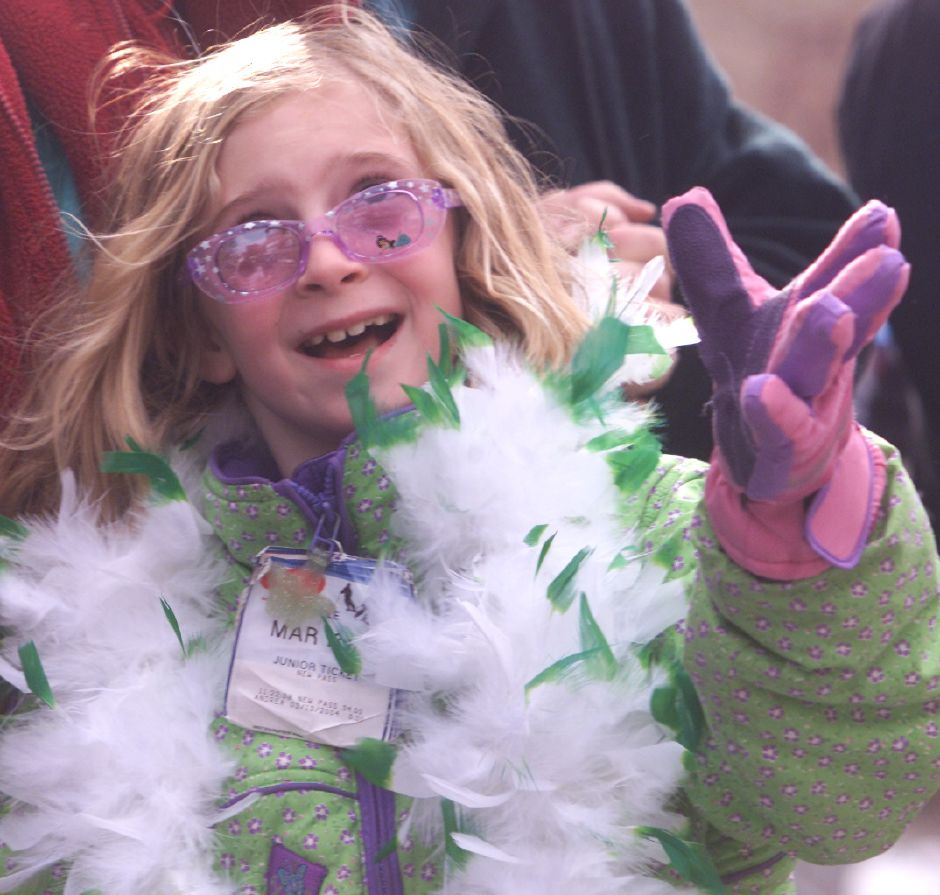 Audry Conklin, 7, reaches for the candy being thrown her way from passing floats at the St. Patrick