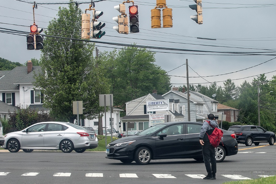 A pedestrian waits to cross at the intersection of Gravel and East Main Streets in Meriden, Wed., June 19, 2019. Dave Zajac, Record-Journal