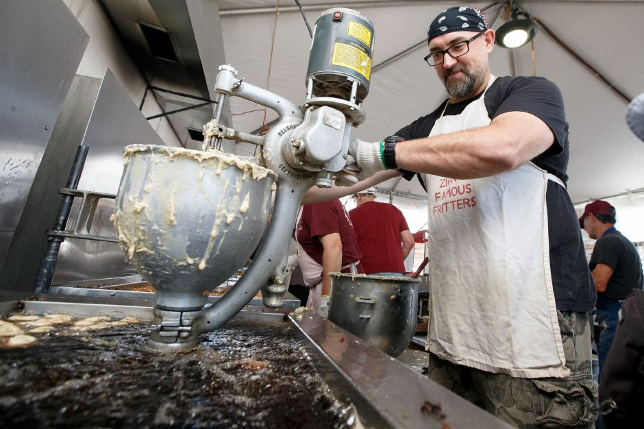 Mike Halloran uses a machine to dispense fritters into the oil to cook Saturday during the Southington Apple Harvest Festival in Southington September 29, 2018 | Justin Weekes / Special to the Record-Journal