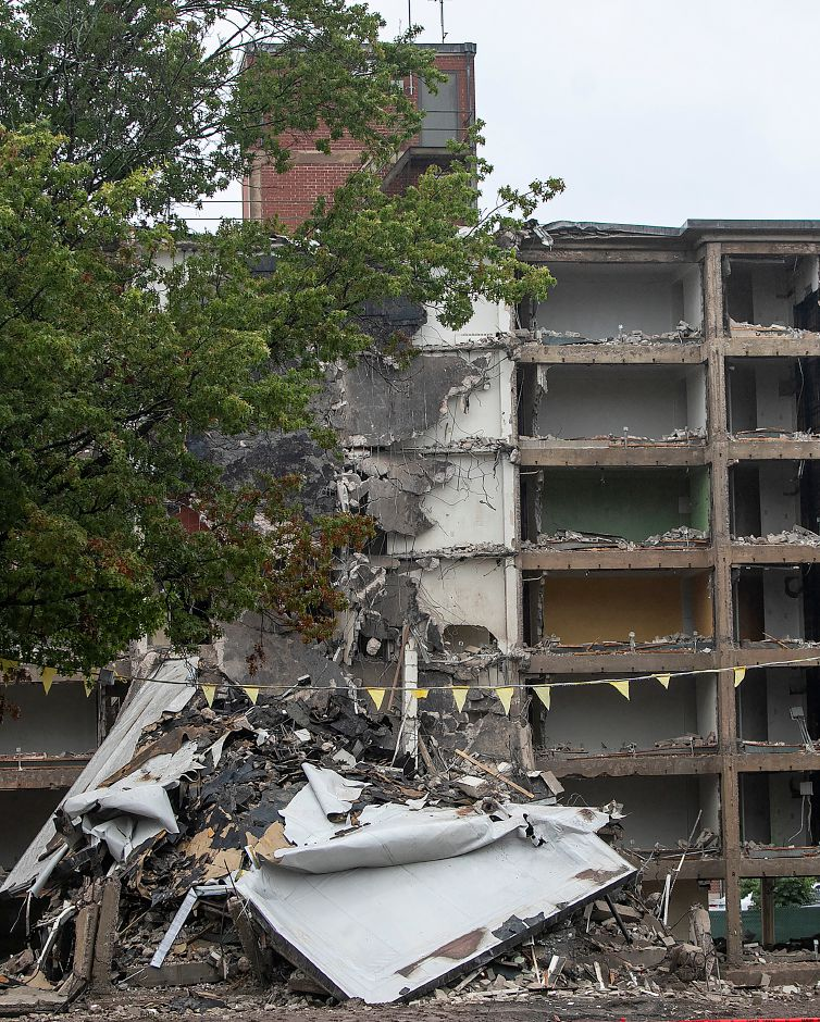 A portion of the former Mills Memorial Apartments lay collapsed after a controlled demolition using a payloader with a steel beam attachment, Monday, Oct. 15, 2018. The payloader strikes at support posts until the building partially collapses. Dave Zajac, Record-Journal