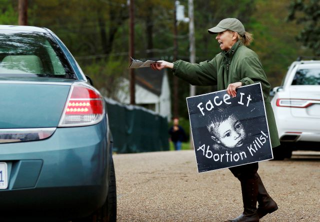 FILE - In this March 20, 2018, file photo, anti-abortion sidewalk counselor Laura Duran, offers reading material to a driver entering the Jackson Women