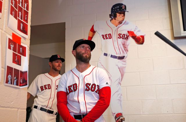 Boston Red Sox second baseman Dustin Pedroia, foreground, and right fielder J.D. Martinez, await their turn for photos during media day at their spring training baseball facility in Ft. Myers, Fla., Tuesday, Feb. 19, 2019. (AP Photo/Gerald Herbert)
