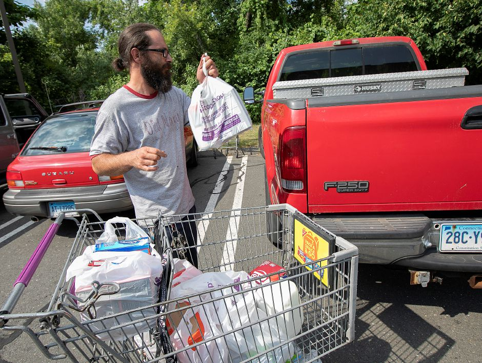 Andrew Sanchez, of Wallingford, packs groceries into his pickup after shopping at Stop & Shop in Wallingford, Mon., July 29, 2019. A change in area supermarkets will require residents to either bring their own bags or purchase paper bags at checkout. Dave Zajac, Record-Journal