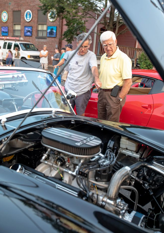 Bob Hubert, left, and Wally Kostrzewa look inside a car during July 10 Music on the Green concern on the Southington Green. The weekly concert series includes a car show each week. | Devin Leith-Yessian/Record-Journal