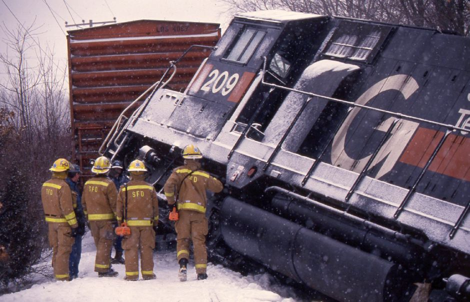 RJ file photo - Rescue workers from the Southington Fire Department inspect the scene of a train derailment north of the Curtiss Street crossing Feb. 23, 1994. Officials say an ice buildup on the track caused the freight train to derail.