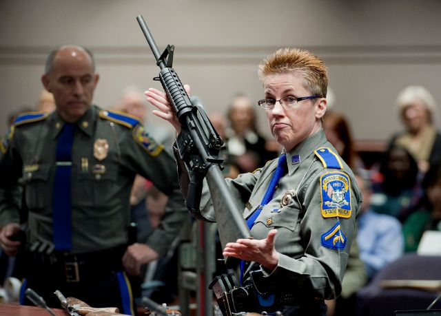 FILE - In this Jan. 28, 2013, file photo, firearms training unit Detective Barbara J. Mattson, of the Connecticut State Police, holds up a Bushmaster AR-15 rifle, the same make and model of gun used by Adam Lanza in the Sandy Hook School shooting, for a demonstration during a hearing of a legislative subcommittee reviewing gun laws, at the Legislative Office Building in Hartford, Conn. The Supreme Court said Tuesday, Nov. 12, 2019, a survivor and relatives of victims of the Sandy Hook...