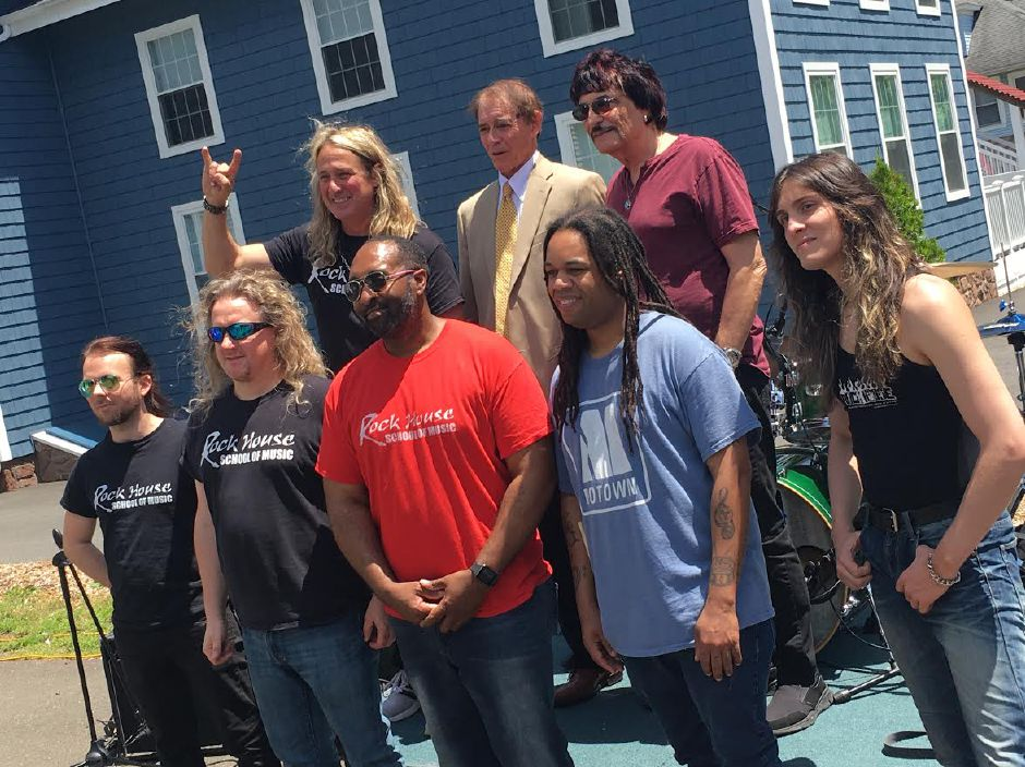 Mayor William W. Dickinson Jr., back center, stands with owner of Rock House School of Music John McCarthy, left, and drummer Carmine Appice, right, and several music instructors at the school's grand opening celebration in Wallingford, June 15, 2019. | Lauren Takores