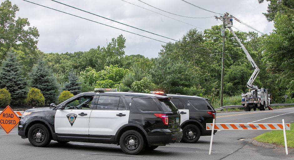 Police block Meriden Avenue in Southington as utility crews work to restore power, Monday, July 23, 2018. More than 1,000 local Eversource Energy customers were without power after police said a tree fell and damaged utility poles and power lines near 905 Meriden Ave. Dave Zajac, Record-Journal
