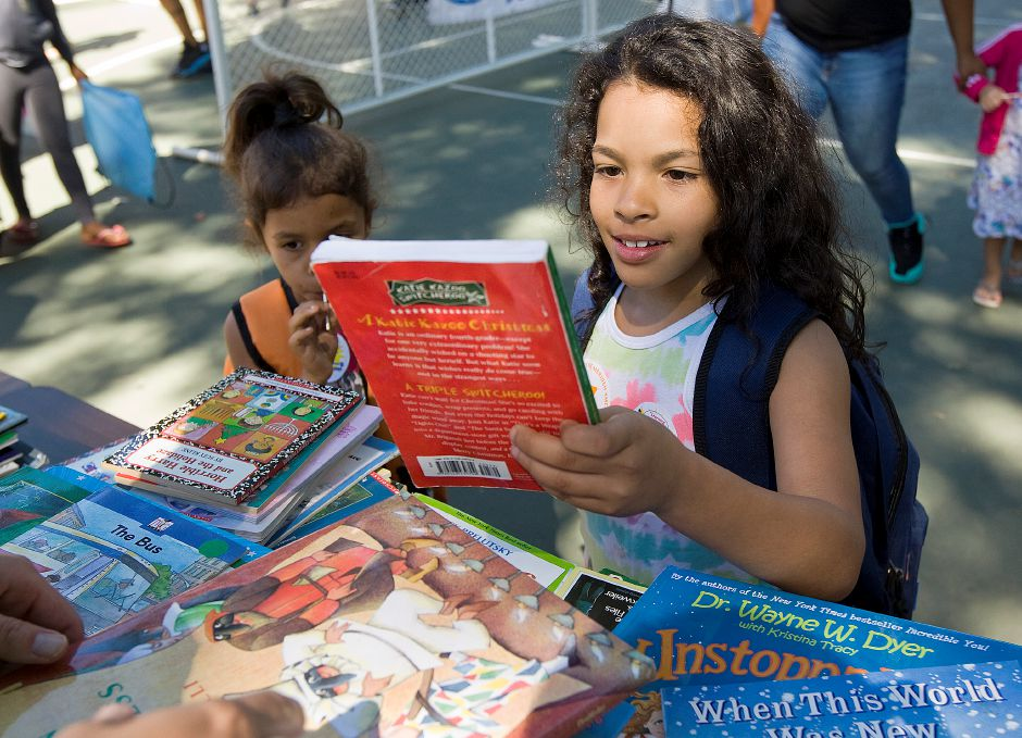 Yumalay Ramos, 8, of Meriden, picks out a book after receiving her new backpack at the annual Back To School Expo at City Park in Meriden, Tuesday, August 23, 2016. | Dave Zajac, Record-Journal