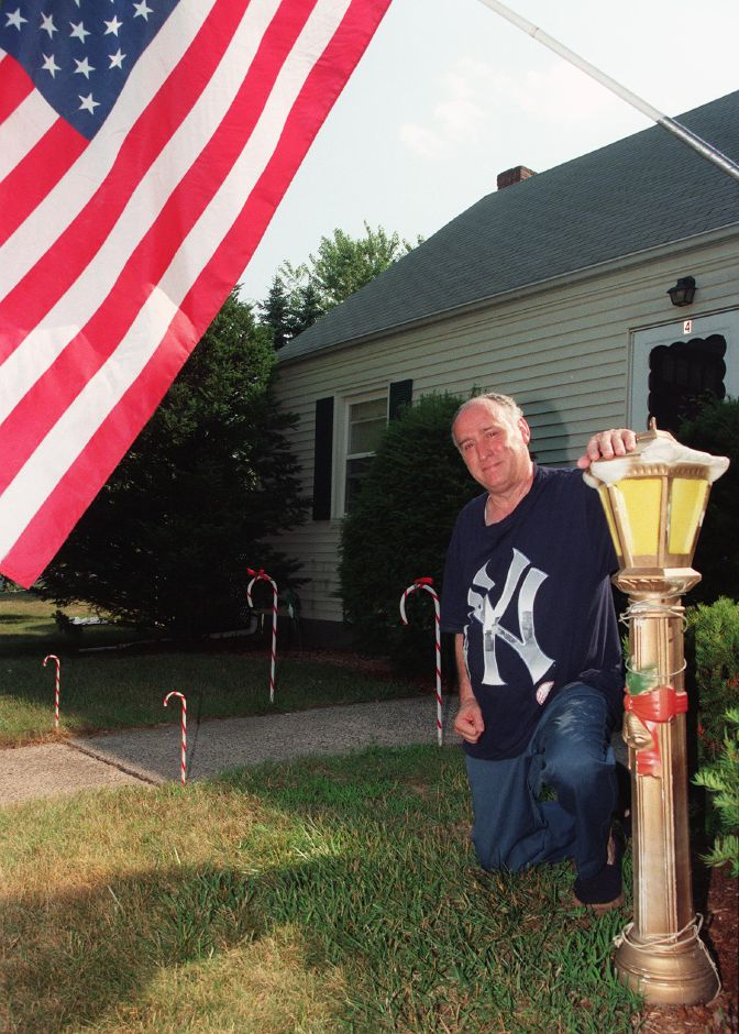 Tony Pasqualoni in front of his Wallingford home Tues., July 6, 1999 with some of his Christmas decorations. He hoped the decorations would give a cool state of mind in the face of the hot days.
