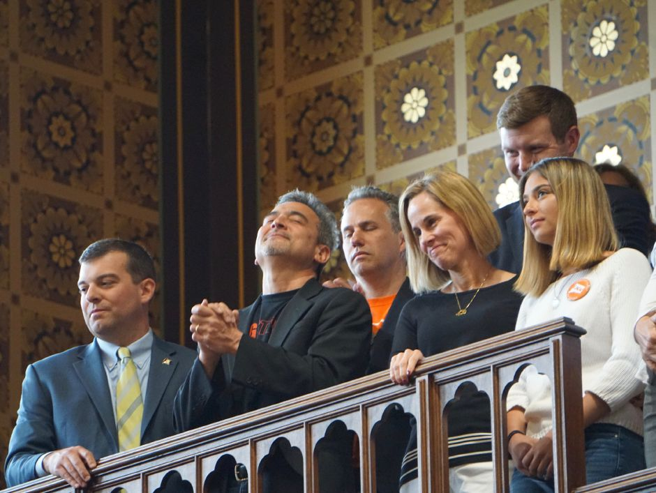 Michael  Song clasps his hands and Kristin Song smiles at final passage of Ethan's Law. At right is their daughter, Emily. With them are Reps. Steven Stafstrom and Sean Scanlon and Jeremy Stein of CAGV. | Mark Pazniokas, The Connecticut Mirror