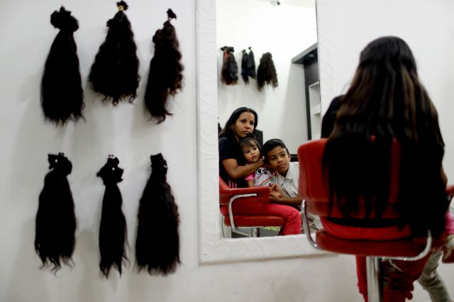 Nelly Navarro sits with her kids Nerianny and Luis in a beauty salon where she came to consult how much money she could get for her hair, in Caracas, Venezuela, Tuesday, April 2, 2019. Navarro said she needs the $100 to travel to Colombia where she