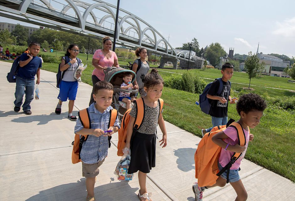 Left to right, Manuel Lopez, 3, Emily Lopez, 5, and Jackline Riddle, 4, of Meriden, walk the Meriden Green with their new orange backpacks after attending the annual Back-to-School Expo, Tuesday, August 22, 2017. | Dave Zajac, Record-Journal