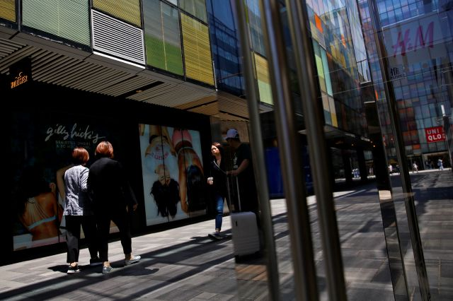 Shoppers walk by foreign fashion boutiques at the capital city