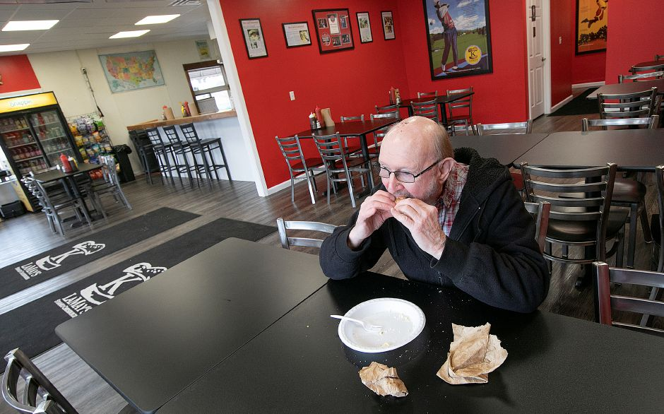 George Koczon, of Meriden, finishes the last bite of a steamed cheeseburger at the newly expanded K. LaMay's Steamed Cheeseburgers restaurant.
